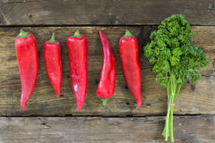 Red sweet pointed peppers in a row and parsley on rustic wood Royalty Free Stock Images