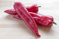 Red sweet pointy peppers (capsicum). Three red sweet pointy peppers (capsicum) on a wooden board stock image
