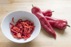 Red sweet pointy peppers and diced peaces in a white bowl on a w. Three red sweet pointy peppers(capsicum) and diced peaces in a white bowl, all on a wooden royalty free stock photos