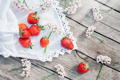 Red sweet strawberries and wildflowers on old wooden eco background. Summer healthy eating concept. Flat lay, top view Stock Photos