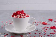 Red sweet sugar candy hearts in a coffee cup. Love and Valentine s day concept decoration. Festive background royalty free stock photography