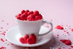 Red sweet sugar candy hearts in a coffee cup. Love and Valentine`s day concept. Festive background stock images