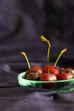 Red sweetheart cherries (grown in England) in a rustic glass bowl on a blue silk background with copy space. Selective focus. Stock Image