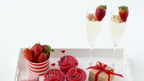 Red sweets and champagne in st valentines day. Valentines day, sweets and romantic concept - frosted cupcakes, macarons with strawberries, champagne glasses and stock video