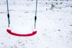 Red swing covered with snow. A red swing covered with snow in a garden Royalty Free Stock Image
