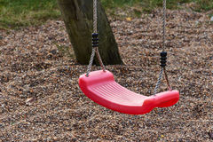 Red swing on playground. Lonely red swing on playground Stock Photos