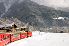 A red swiss train running through the snow. Royalty Free Stock Photography