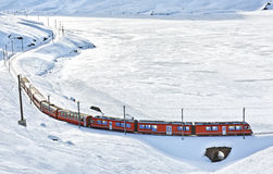 A red swiss train running through the snow Stock Photo