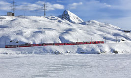 A red swiss train running through the snow Royalty Free Stock Photo
