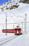 A red swiss train running through the snow, Switzerland. Stock Photo