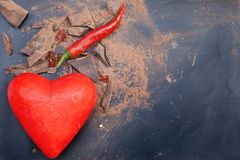 Red symbol of heart and chili peppers and dark chocolate piece Royalty Free Stock Photography