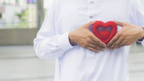 The red symbol heart on the hand of priest Royalty Free Stock Photography