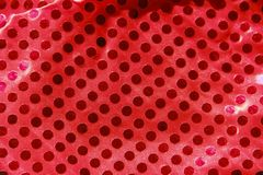 Festive red synthetic fabric with round shiny sequins. Red synthetic fabric with round shiny sequins royalty free stock photos