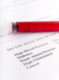 Red Syringe and Medical Survey Royalty Free Stock Photos