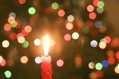 Red tänt stearinljus med suddigheta lampor Arkivfoton