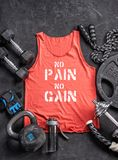 Red t-shirt and sports equipment on a black background. Top view. Motivation. Copy space Royalty Free Stock Photos