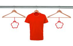 Red t-shirts on hangers and blank tags isolated on white Royalty Free Stock Photo