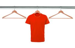 Red t-shirts on hangers isolated on white Royalty Free Stock Photos
