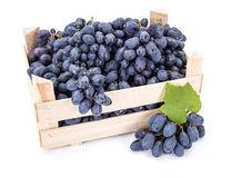 Red table grapes (Vitis) in wooden crate. On white Stock Photo