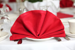 Red table napkin. On top of porcelain plate Royalty Free Stock Photography