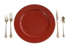 Red Table Setting. Table setting with red plate and silverware on white Royalty Free Stock Photo
