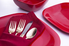 Red Table Setting. A table setting with red plates and bowl, a red napkin folded into a silverware pouch and gold silverware Royalty Free Stock Photos