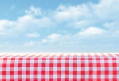 Red tablecloth in a cage on a pile, in the background a sky with clouds Stock Image