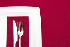 Red tablecloth with white plates Royalty Free Stock Images