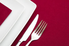 Red tablecloth with white square plates Stock Photo