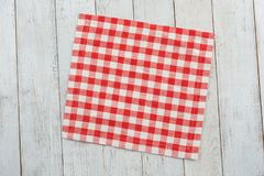 Red tablecloth on white wooden table background. Stock Photography