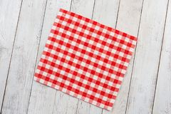 Red tablecloth on white wooden table background. Stock Image