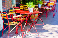 Red tables and chairs at a sidewalk cafe at european city Royalty Free Stock Photo