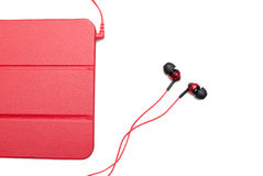 Red tablet and earphone plugs Royalty Free Stock Image