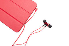 Red tablet and earphone plugs Royalty Free Stock Images