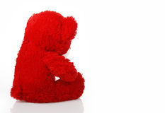 Red taddy bear turned away. On a white background stock photo
