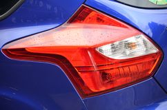 Red Tail Light on Blue Car. This is a red tail light curving with the form of a blue car Stock Photos