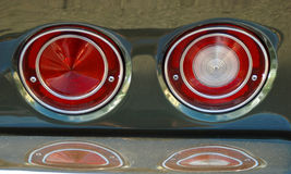 Red tail lights of classic car. Reflected on chrome bumper royalty free stock images