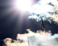 Red-Tailed Hawk in the Sun`s Rays. Red-Tailed Hawk soaring in the sky amidst the clouds and sun`s rays in Fallon, NV Stock Images