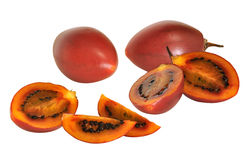 Red tamarillo fruit with cross sections. Sweet red tamarillo fruits with cross sections showing the ripe flesh and seeds stock images