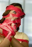 Red Tape. Businesswoman wrapped in red tape Royalty Free Stock Photos
