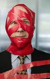 Red Tape. Businessman wrapped in red tape Stock Photography