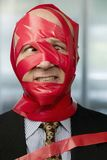 Red Tape. Cross-eyed businessman wrapped in red tape Stock Images