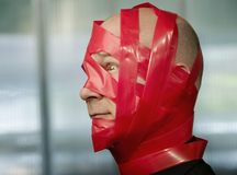 Red Tape. Businessman wrapped in red tape Stock Photo