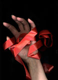 Red Tape. Hand tied in red tape with black background stock images