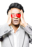 Red tape and business confusion. Asian businessman with his hands to his face and eyes taped shut with red tape conceptual of bureaucratic red tape causing Stock Images