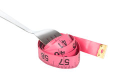 Red tape measure coiled around a fork Stock Photo