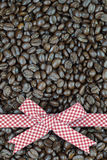 Red tartan ribbon on coffee beans background.  Royalty Free Stock Photo