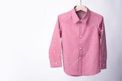 Red tartan shirt folded on white background.  Stock Photo