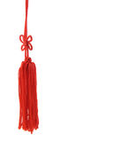 The Red Tassel. Close up detail of isolated red silk tassel on white stock photo