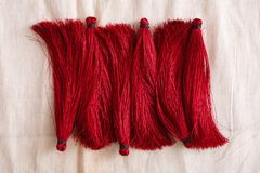 Red tassels line close up. Woman handicraft. Art, creativity, hobby, home workshop concept Royalty Free Stock Photos